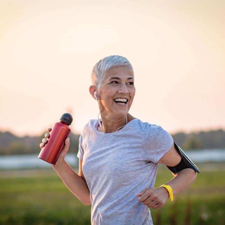 Mulher madura correndo após tomar suplementação de Coenzima Q10