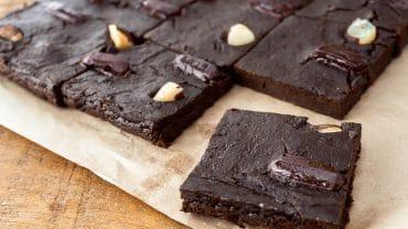 pedaços de brownie sem açúcar em uma mesa de madeira, sob um papel pardo