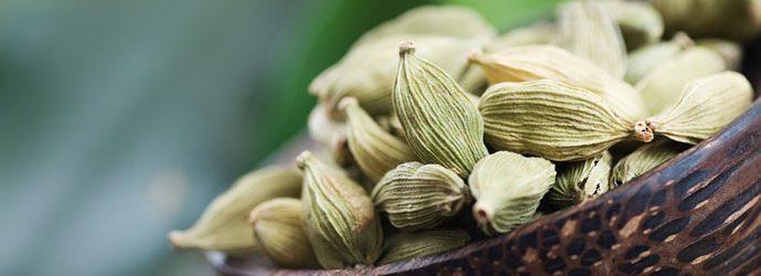 sementes de cardamomo em uma pequena tigela com textura de madeira