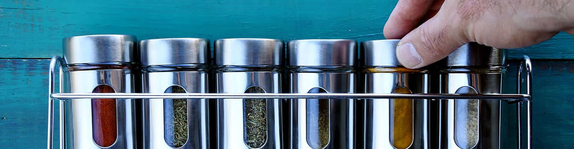 Mão escolhe potes com especiarias em uma prateleira