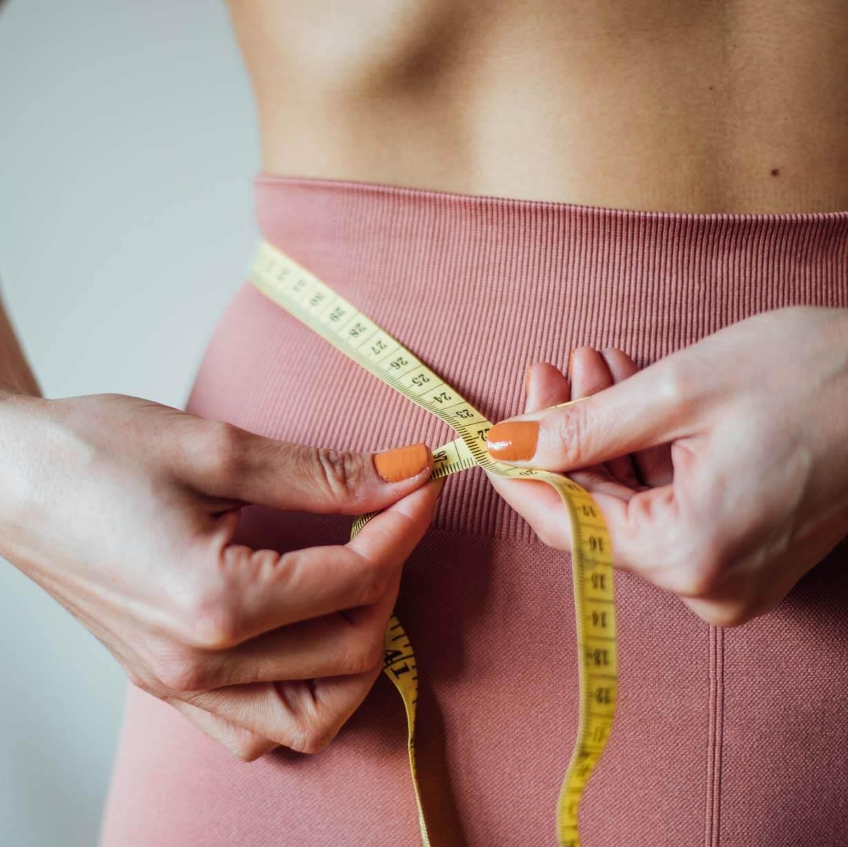 Mulher medindo a cintura com fita métrica