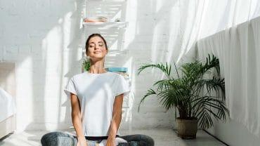 garota feliz de olhos fechados praticando ioga em posição de lótus no quarto pela manhã