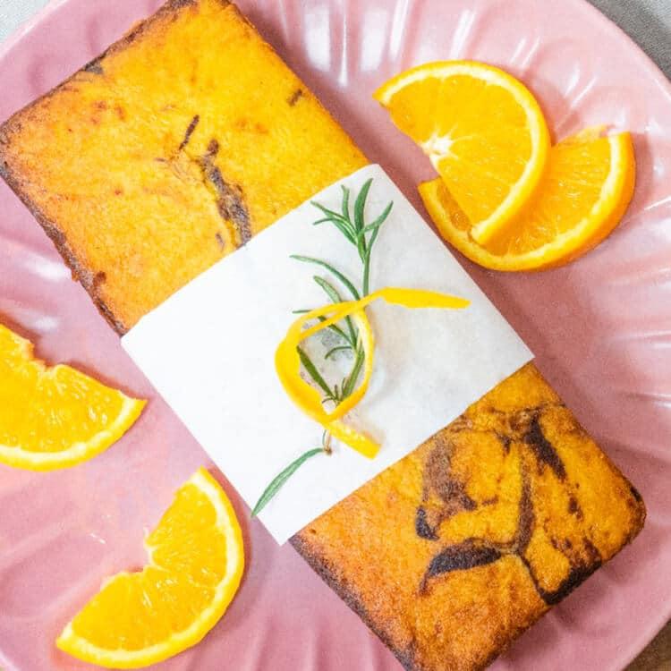 bolo de laranja mesclado servido em um prato rosa com rodelas de laranja