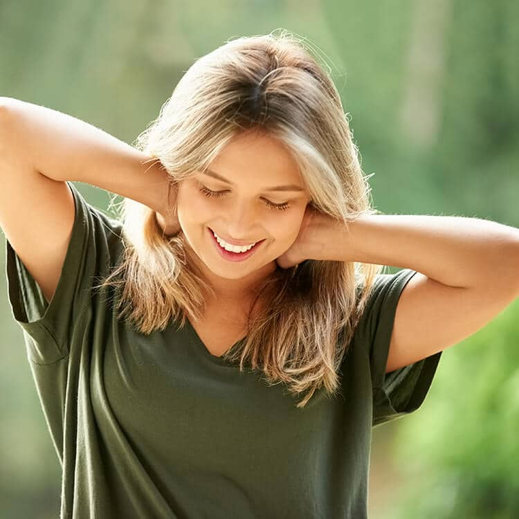 Mulher sorri enquanto leva as mãos ao pescoço