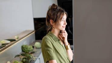 Mulher de perfil, olhando para a geladeira aberta na cozinha de casa.