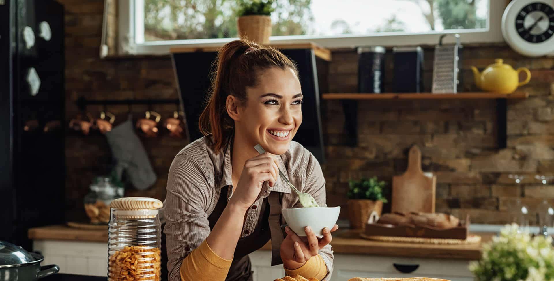Jovem mulher sorridente, desfrutando ao fazer uma refeição na cozinha. Ela segura uma colher e uma tigela apoiada na bancada
