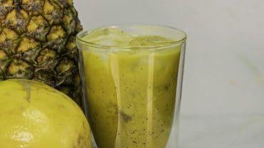 copo de vidro com suco revitalizante, ao lado de um abacaxi e um maracujá